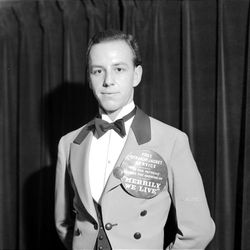 """An usher of a downtown theater greeting patrons, his button is promoting the movie currently showing """"Merrily We Live"""" in 1938."""