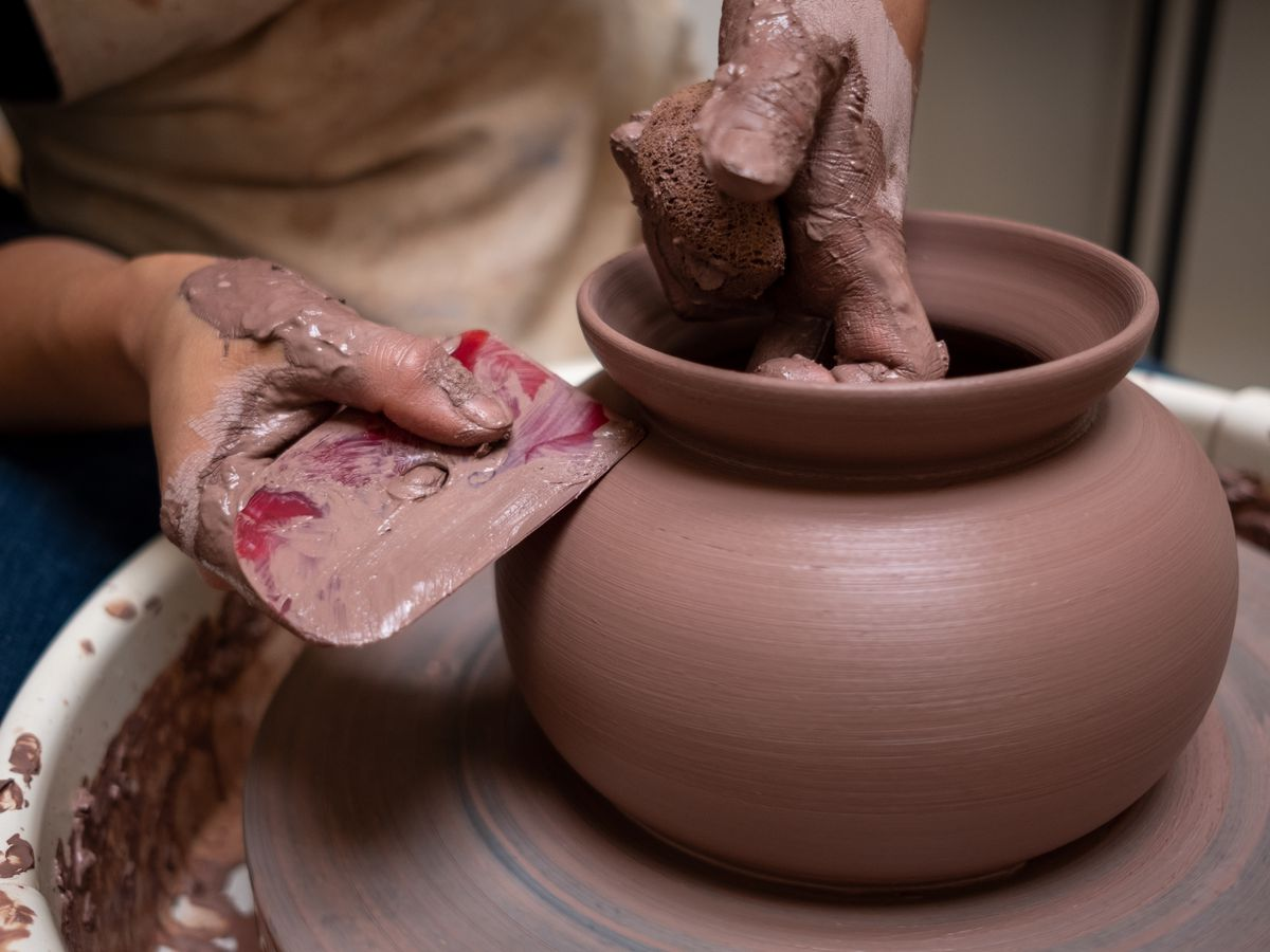 A woman's hands molding raw clay into a rimmed pot on a pottery wheel.
