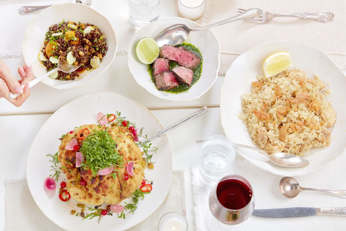 An overhead shot of four white bowls filled with grains, cauliflower, and ribeye steak. Off-screen to the left, a hand holds a spoon