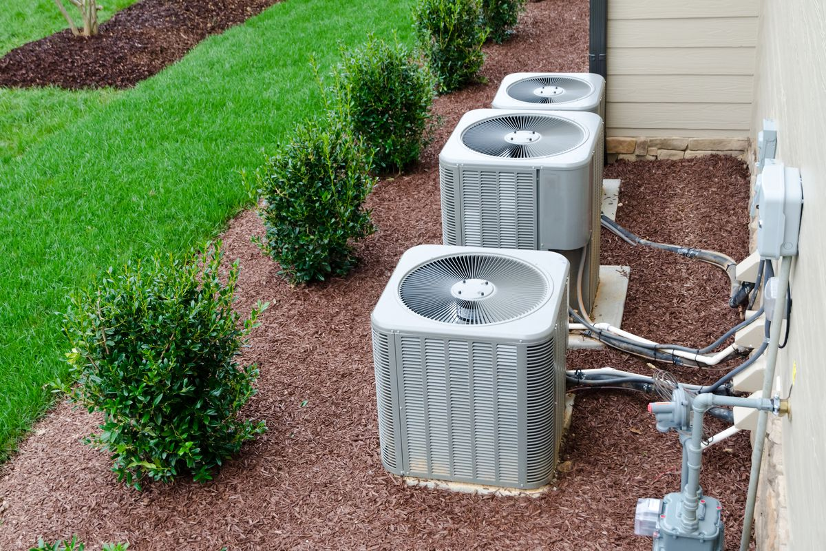 AC units behind a white home sitting in brown mulch near small green shrubs and green grass.