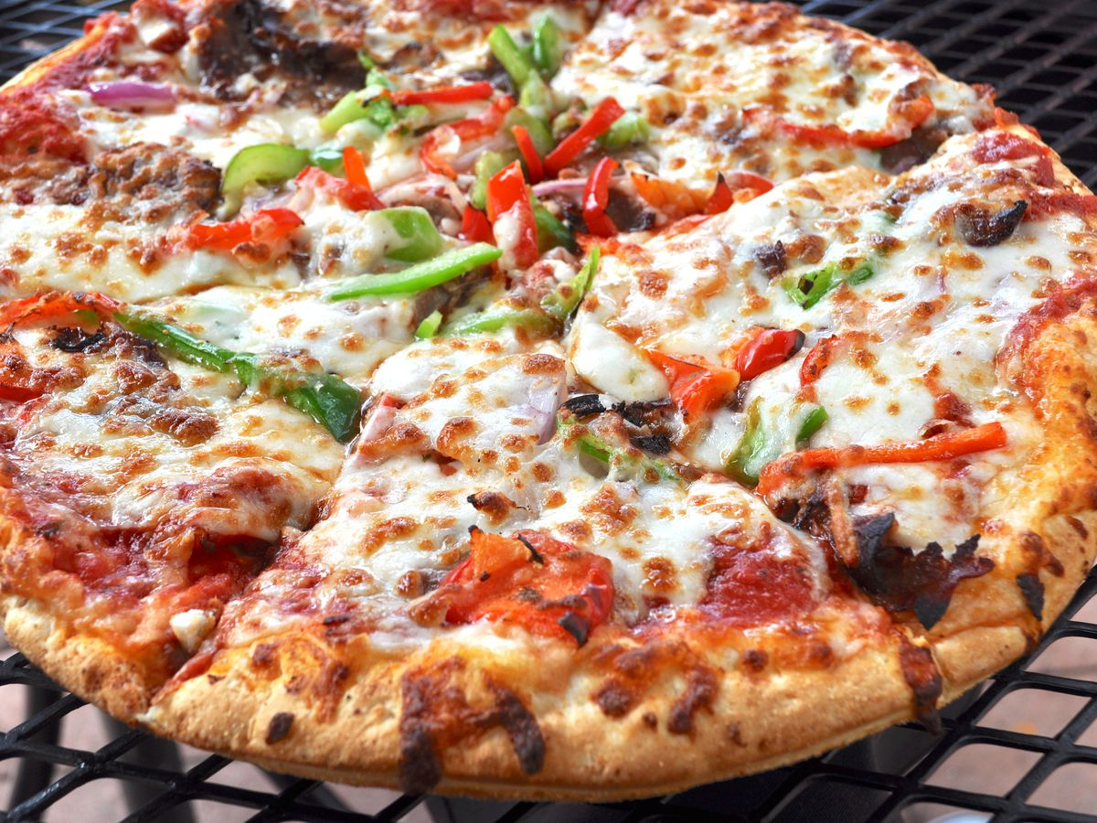 Pizza with shaved steak, peppers, and onions