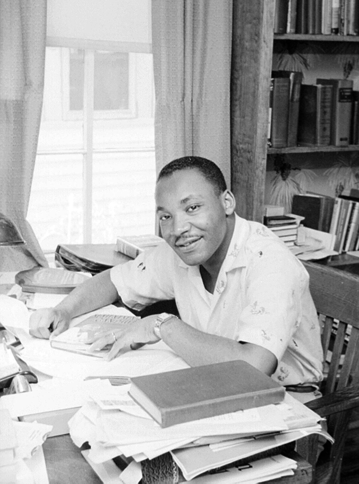 A young black man smiles in an archival black and white photo. He is leaning over his desk that is covered in paper and books, with his hand on a journal.