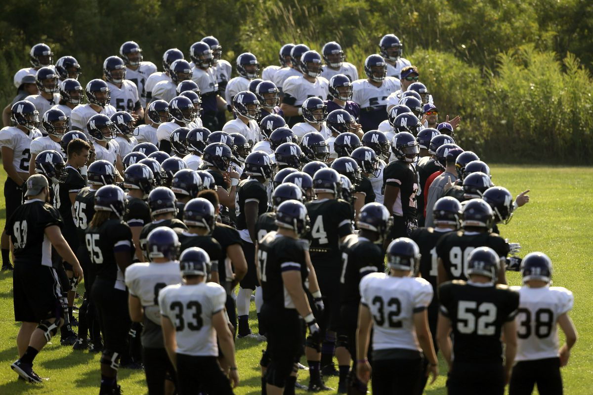 Northwestern football players gather during practice in this 2015 file photo. College football players and some other athletes are employees of their schools, the National Labor Relations Board's top lawyer said in a memo.