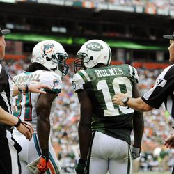 Miami Dolphins cornerback Richard Marshall (31) and New York Jets wide receiver Santonio Holmes (10) engage each other as head linesman Greg Maxwell (67) and another official attempt to restrain them during the second half of an NFL football game, Sunday, Sept. 23, 2012, in Miami.