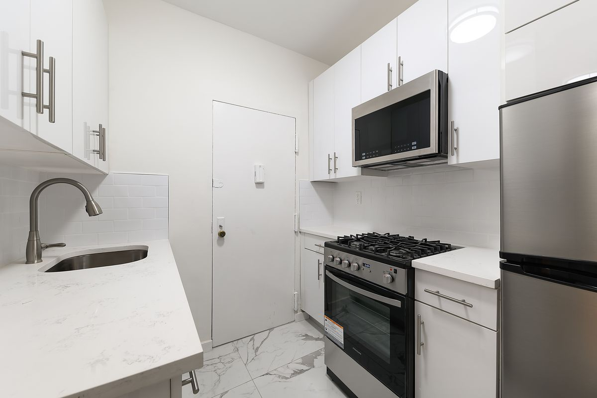 A small kitchen with white cabinetry.