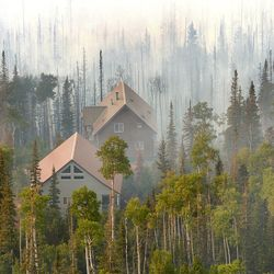 FILE - Fire burning at Brian Head ski resort east of Cedar City, Utah  Many homes and structures were threatened. A fire that began with the use of a weed torch in dry conditions tripled overnight Tuesday.