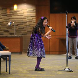 Carol Wang, 9, sings the national anthem as her mother, Sui Zhang, records her during tryouts at EnergySolutions Arena in Salt Lake City on Friday, Oct. 4, 2013. The winners will perform the anthem prior to each Utah Jazz home game during the 2013-2014 season.