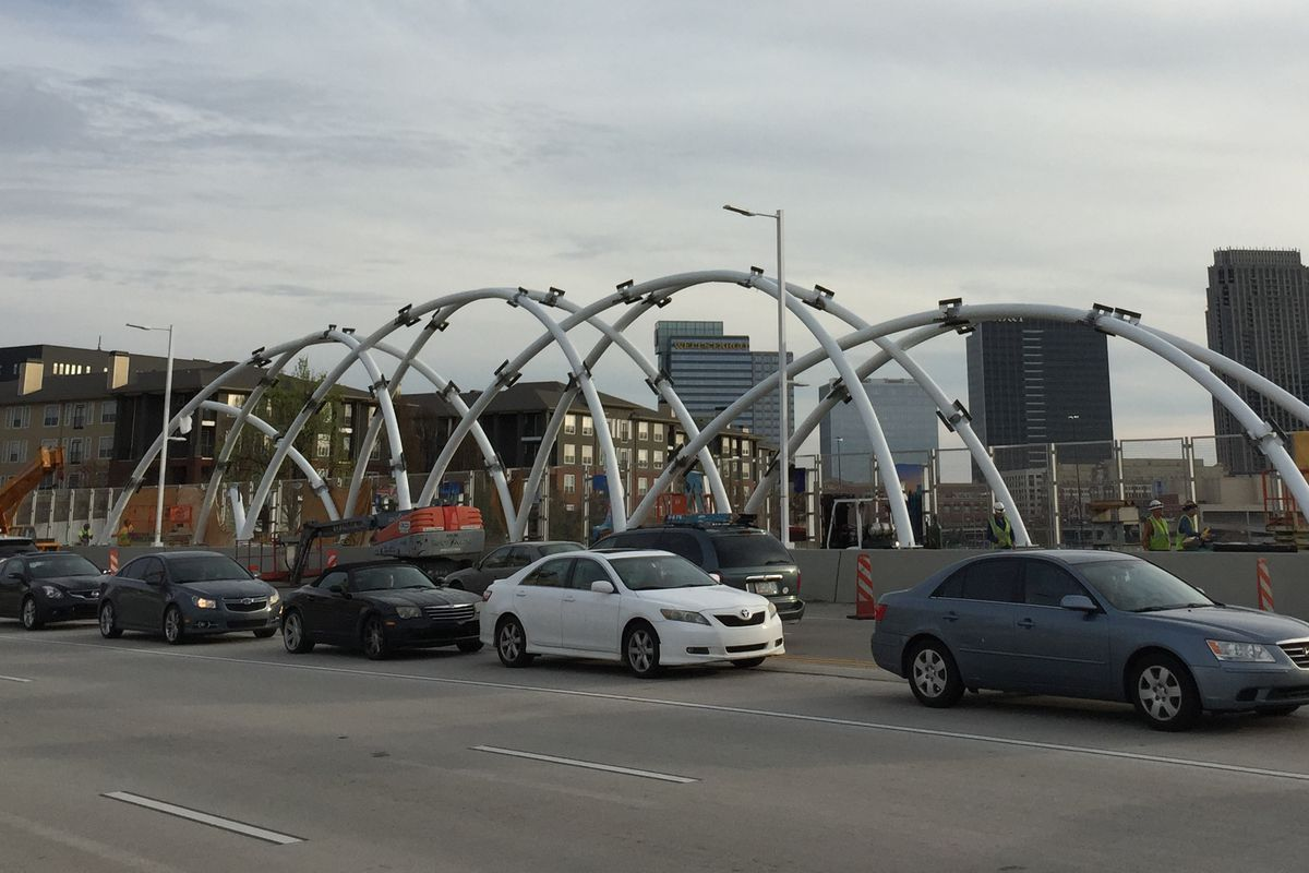 Large white metal arches spanning the sidewalk of the bridge.