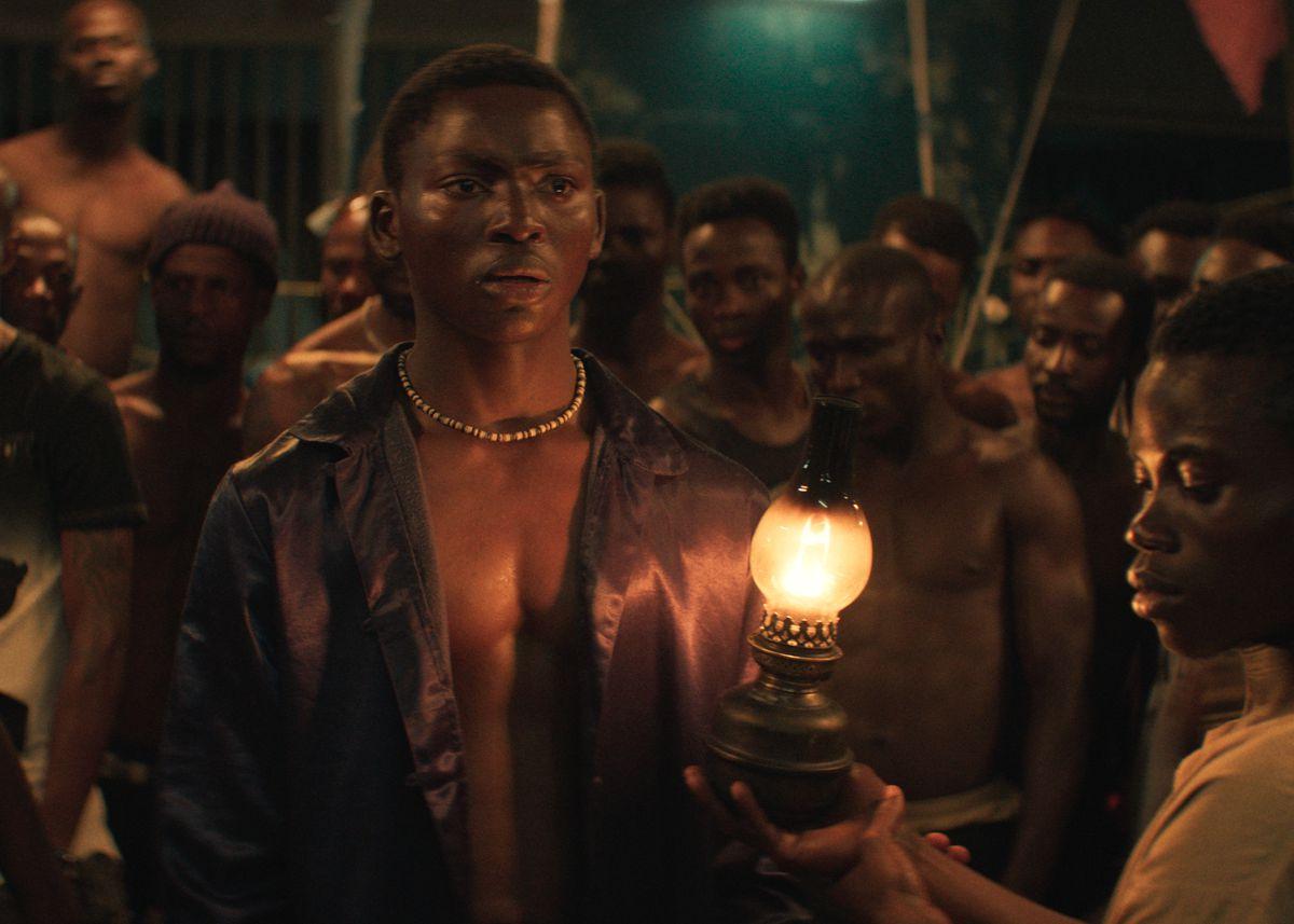 un jeune homme entouré d'une foule dans la nuit des rois
