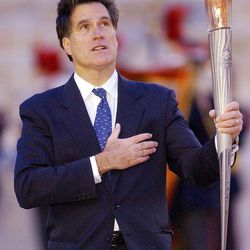 Mitt Romney holds the Olympic torch during the U.S. national anthem in Athens, Greece, Dec. 3, 2001.