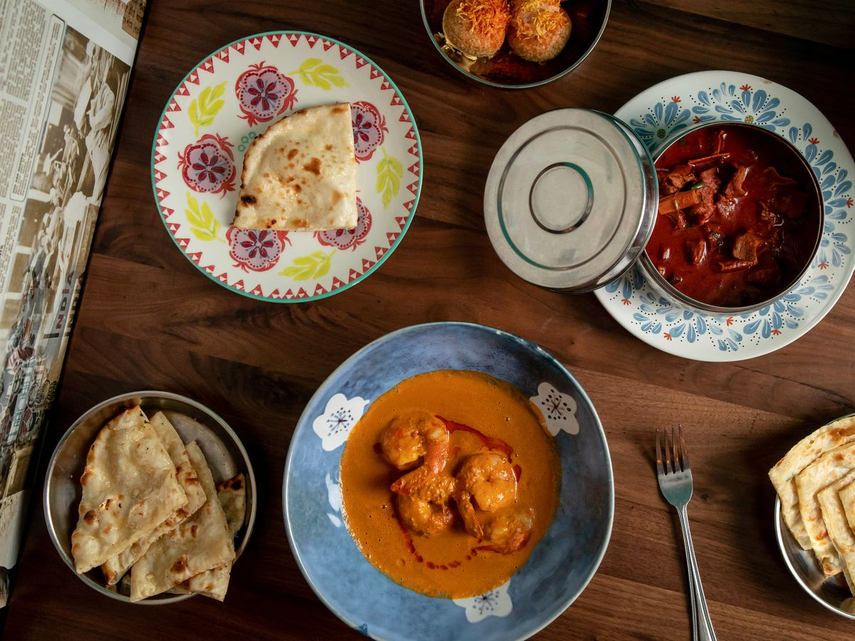 Several colorful Indian dishes seen from above.