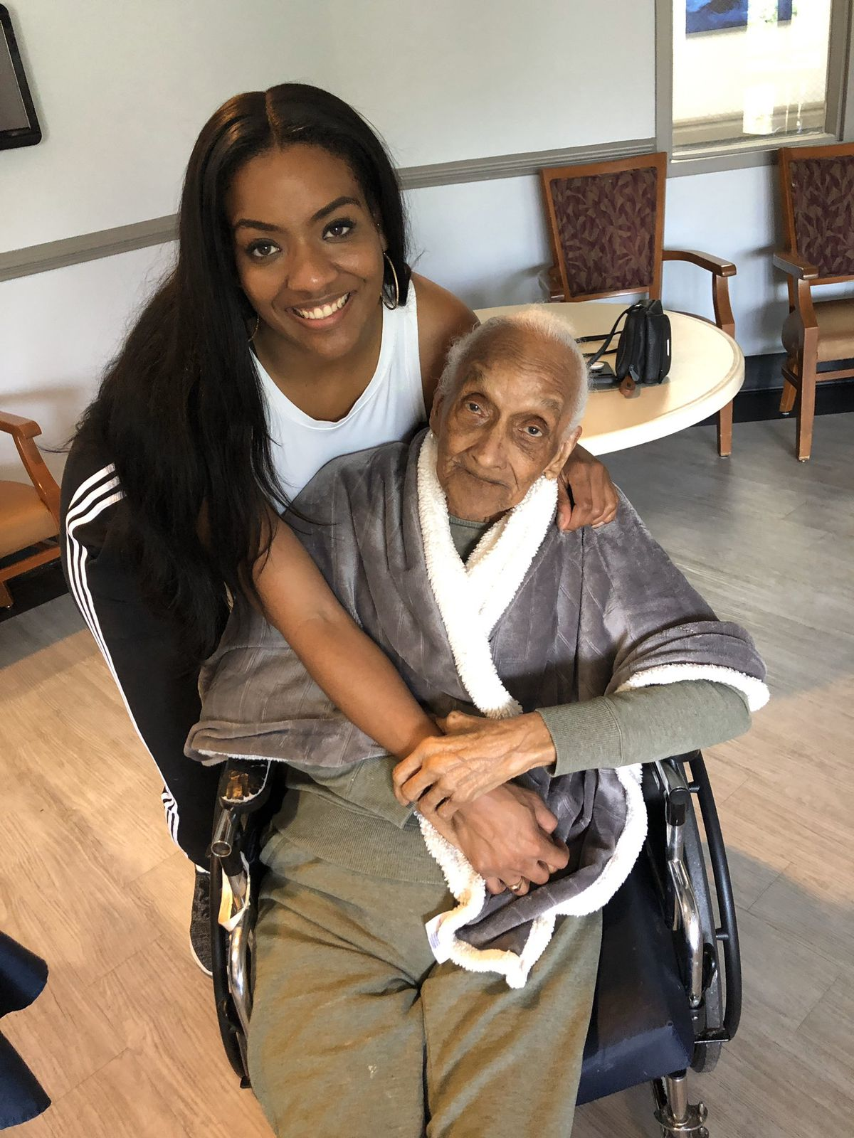 Janel Forte is posing with her grandmother in a wheel chair.