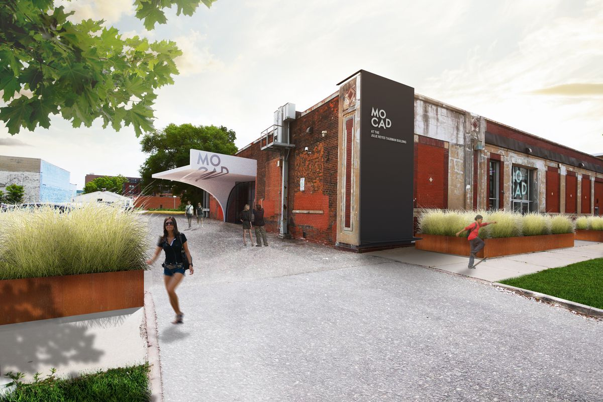 """An image of a long one-story building with red and black paint. There's a geometrical awning over the entrance with """"MOCAD"""" printed on it."""