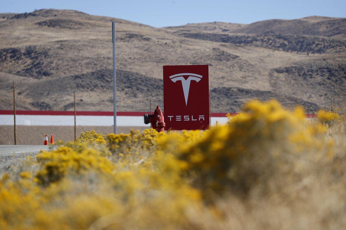 A Tesla sign in front of desert hills.