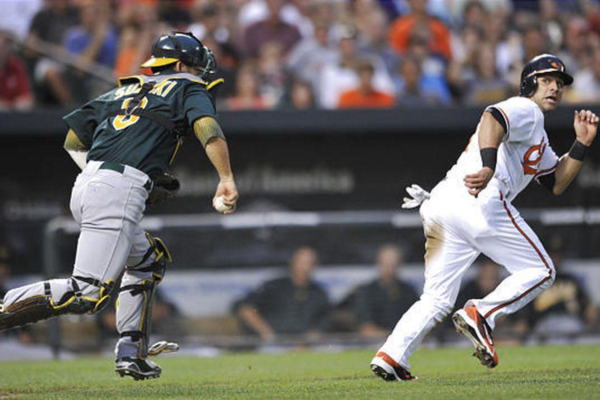 Brian Roberts is caught in a run down as Athletics catcher Kurt Suzuki chases.
