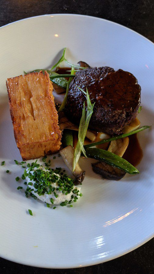 The beef tenderloin adorned with a potato pave, mushrooms, and a horseradish cream