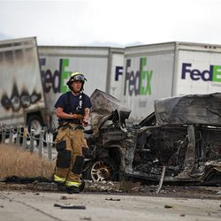 Firefighter walks past burned wreckage of Dodge Dakota that collided with a FedEx semitruck Saturday on I-80 near the Salt Lake-Tooele border, killing the driver of the Dakota and injuring the FedEx driver. The fiery crash shut down I-80 in both directions for four hours.