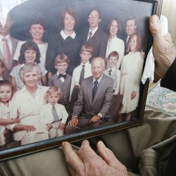 Roger Thompson, 99, looks over an old family photo at his home in Salt Lake City Friday, Dec. 3, 2013.