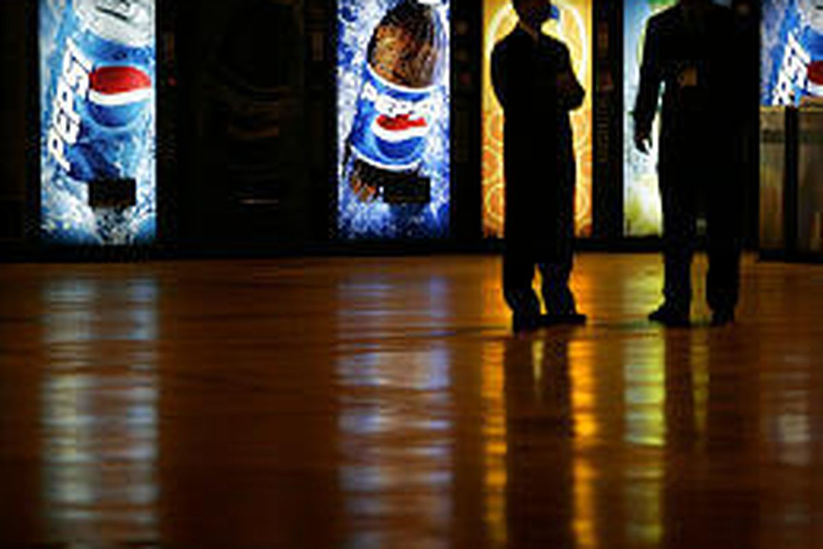 Two men stand near Pepsi machines at the IX Center in Cleveland, Ohio. PepsiCo expects to exceed what it had forecast for full-year profits.