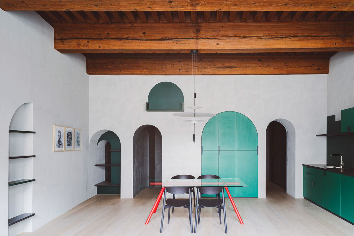 Airy apartment with exposed beam ceilings, white walls, arched doorways, and green kitchen cabinets.