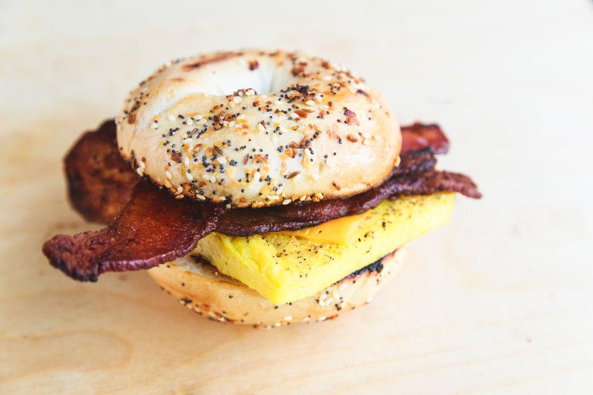 A bagel sandwich with strips of bacon, a square piece of cooked egg, and cheese