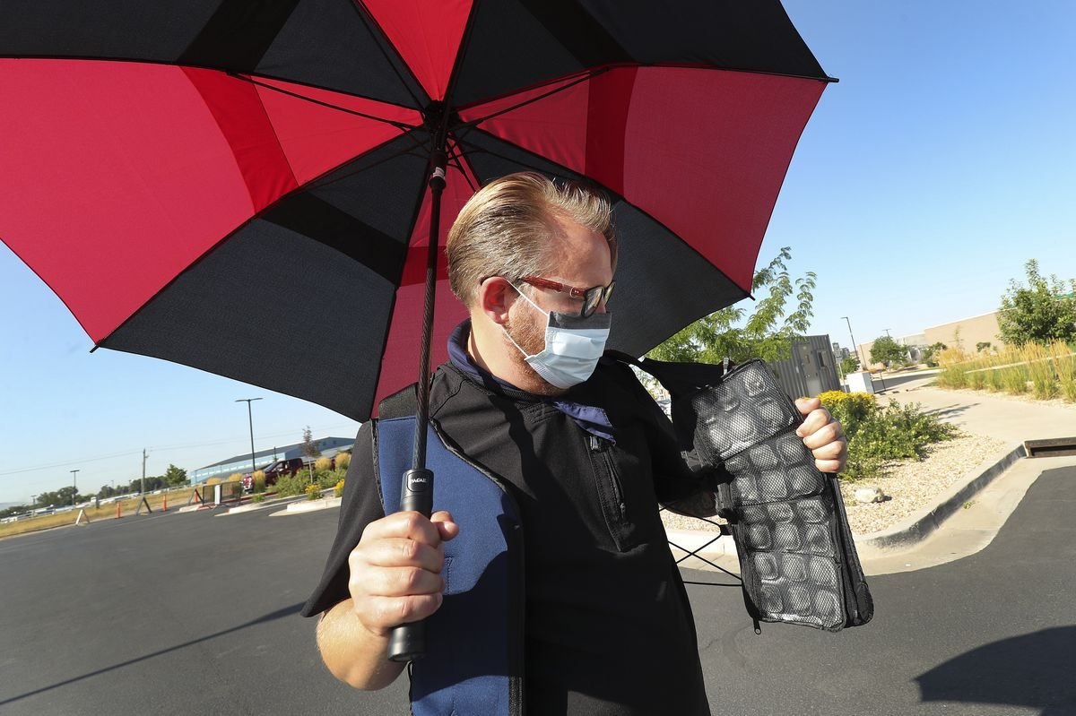 Traffic controller Mike Green shows his FlexiFreeze cooling vest as University of Utah Health workers test for COVID-19 in Farmington on Friday, July 31, 2020. U of U Health is using cooling methods to keep employees comfortable while working in the extreme heat.