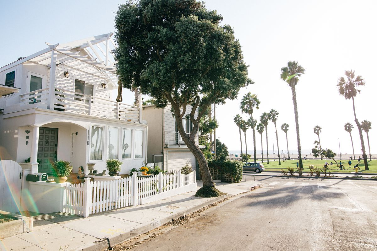 A sunny corner of a block in Santa Monica, with a white house, white picket fence, and tree in front. There is a park with grass and palm trees in the background with the beach behind it.