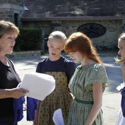 In this photo made on Tuesday, Sept. 11, 2012, author Mary Frailey-Calland, left, goes over the script with CLO Academy of Musical Theater students, Victoria Huston, left center, Chelsea Calfo, center right, and Johanna Loughran during a rehearsal for a dramatic reading in front of the old powder magazine building in Arsenal Park in Pittsburgh. Frailey-Calland wrote the script for the reading that is part of a planned day of memorial services scheduled for Sunday, Sept. 16, 2012 in recognition of the Sept. 17th anniversary of what is thought to be the largest loss of civilian life on a single day in the Civil War. Frailey-Calland also wrote a novel about the explosions at the laboratory where cartridges for union soldiers were being assembled at the Allegheny Arsenal in 1862, killing 78 people, mostly teenage girls who worked there.