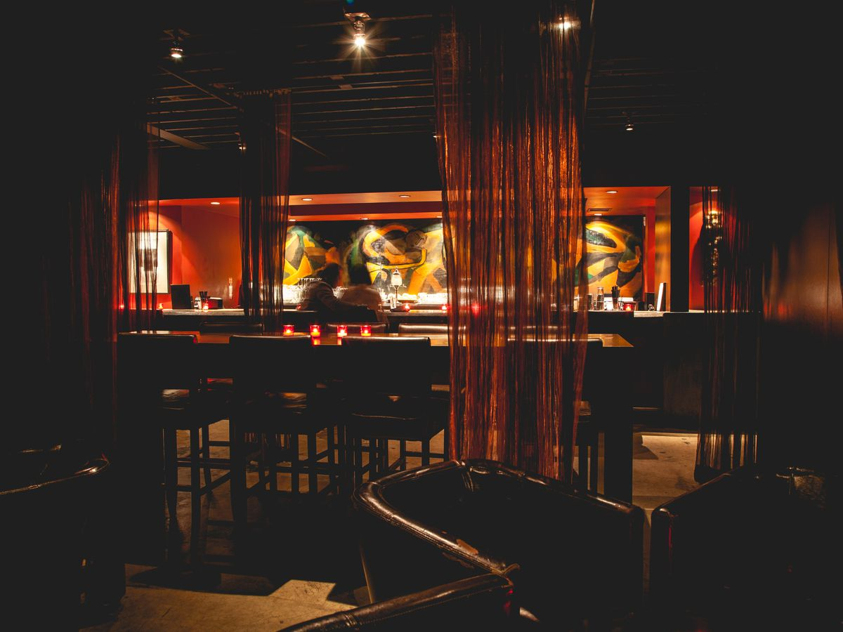 A dark interior of a bar with art hanging on a red wall behind the back bar
