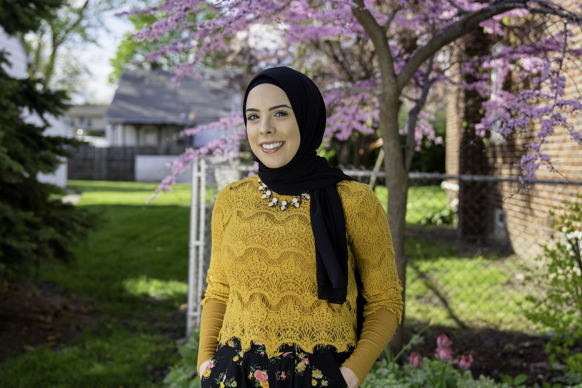 Lena Sareini stands in a yard with a black headscarf on, a yellow sweater, and black pants with a floral print.