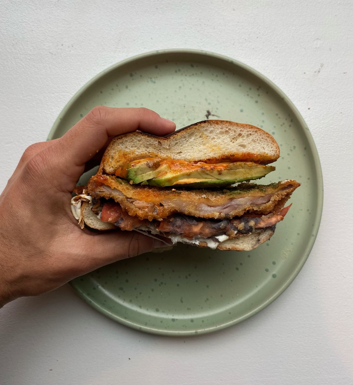 An overhead photograph of a brown hand squeezing a multi-layer torta over a mint-green plate