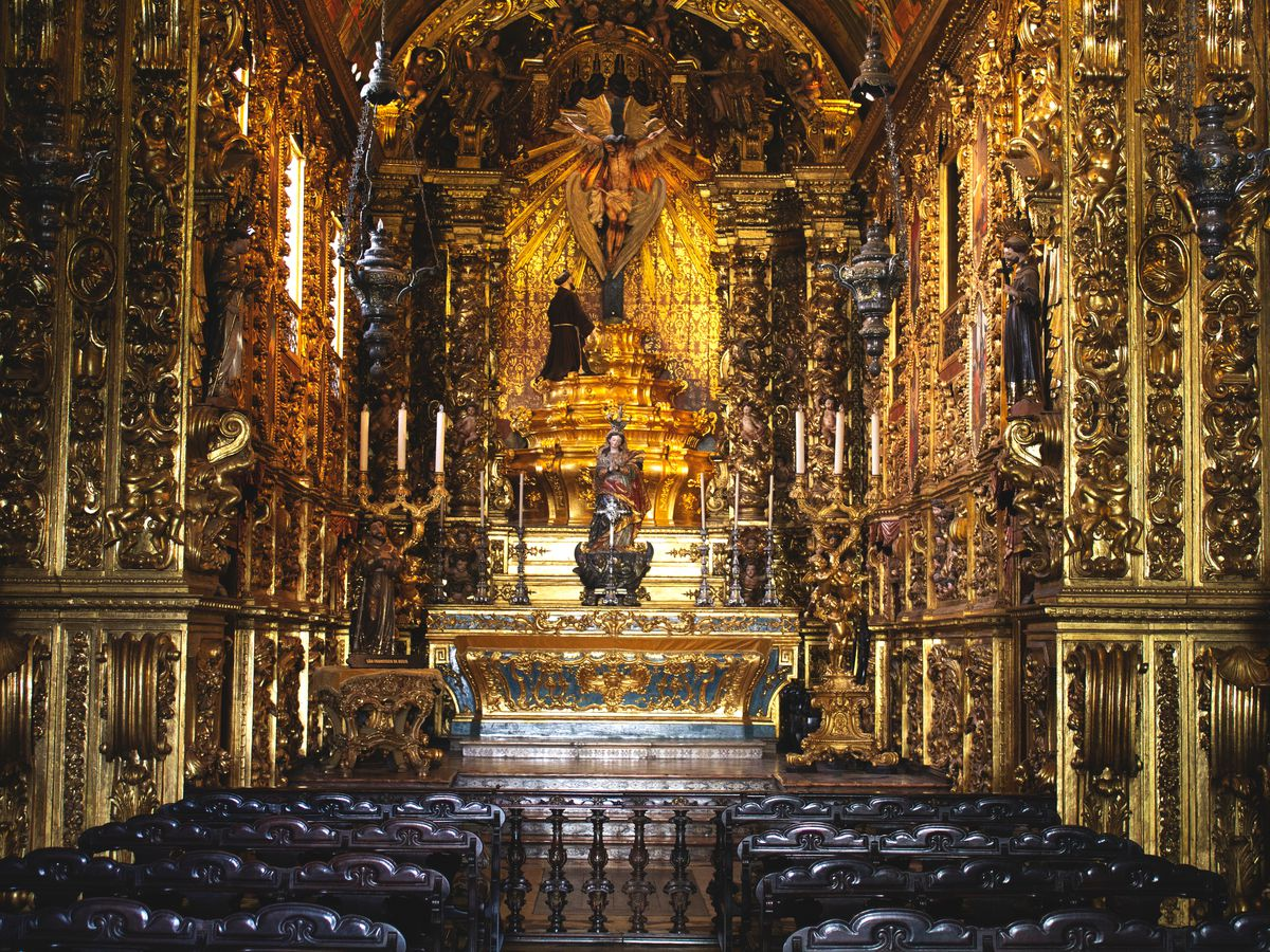 The interior of the Monastery of Sao Bento in Rio de Janeiro. The walls are ornately decorated and there are rows of seats. The altar is gold.