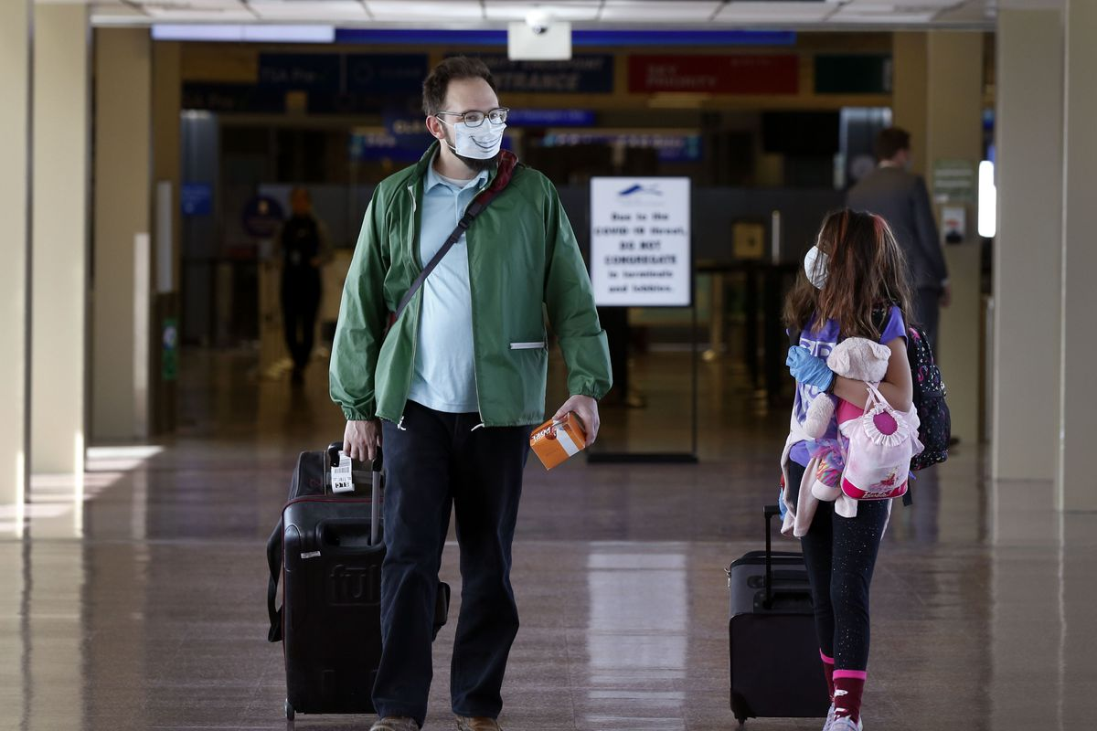 """Matt Lemmon and his daughter Celeste walk through the Salt Lake City International Airport on Wednesday, April 8, 2020. Utah Gov. Gary Herbert announced new efforts on Wednesday """"to protect the people of Utah and slow the spread of coronavirus in the state"""" by closely monitoring its borders, as well as passengers who fly into the Salt Lake International Airport."""