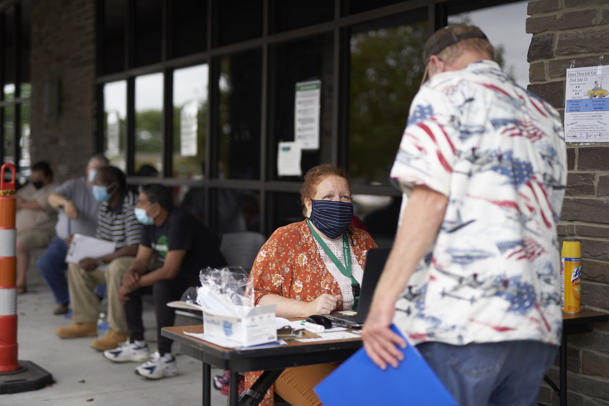 In this July 15, 2020, file photo, One-stop operator Vickie Gregorio with the Heartland Workforce Solutions talks to a jobseeker outside the workforce office in Omaha, Neb., as others seeking employment wait behind her.