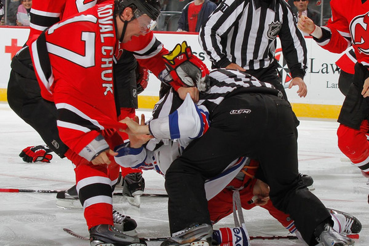 Ilya Kovalchuk of the Devils bravely takes on Sean Avery of the Rangers. While the ref is holding Avery down naturally.