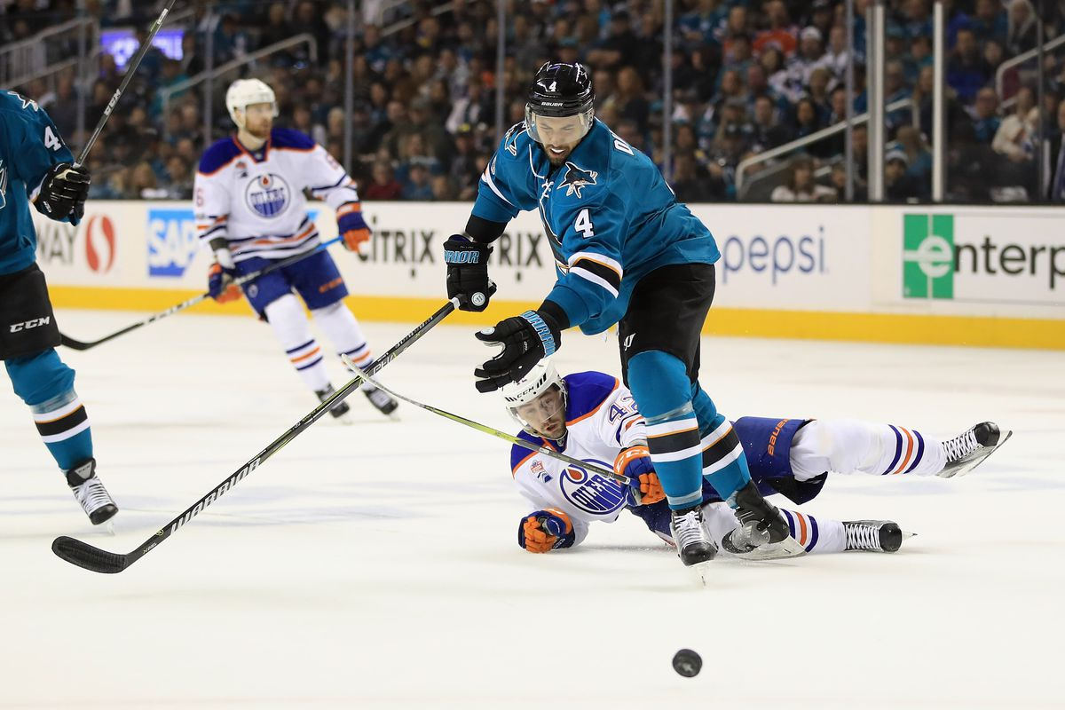 SAN JOSE, CA - APRIL 22: Brenden Dillon #4 of the San Jose Sharks and Anton Slepyshev #42 of the Edmonton Oilers go for the puck during Game Six of the Western Conference First Round during the 2017 NHL Stanley Cup Playoffs at SAP Center on April 22, 2017