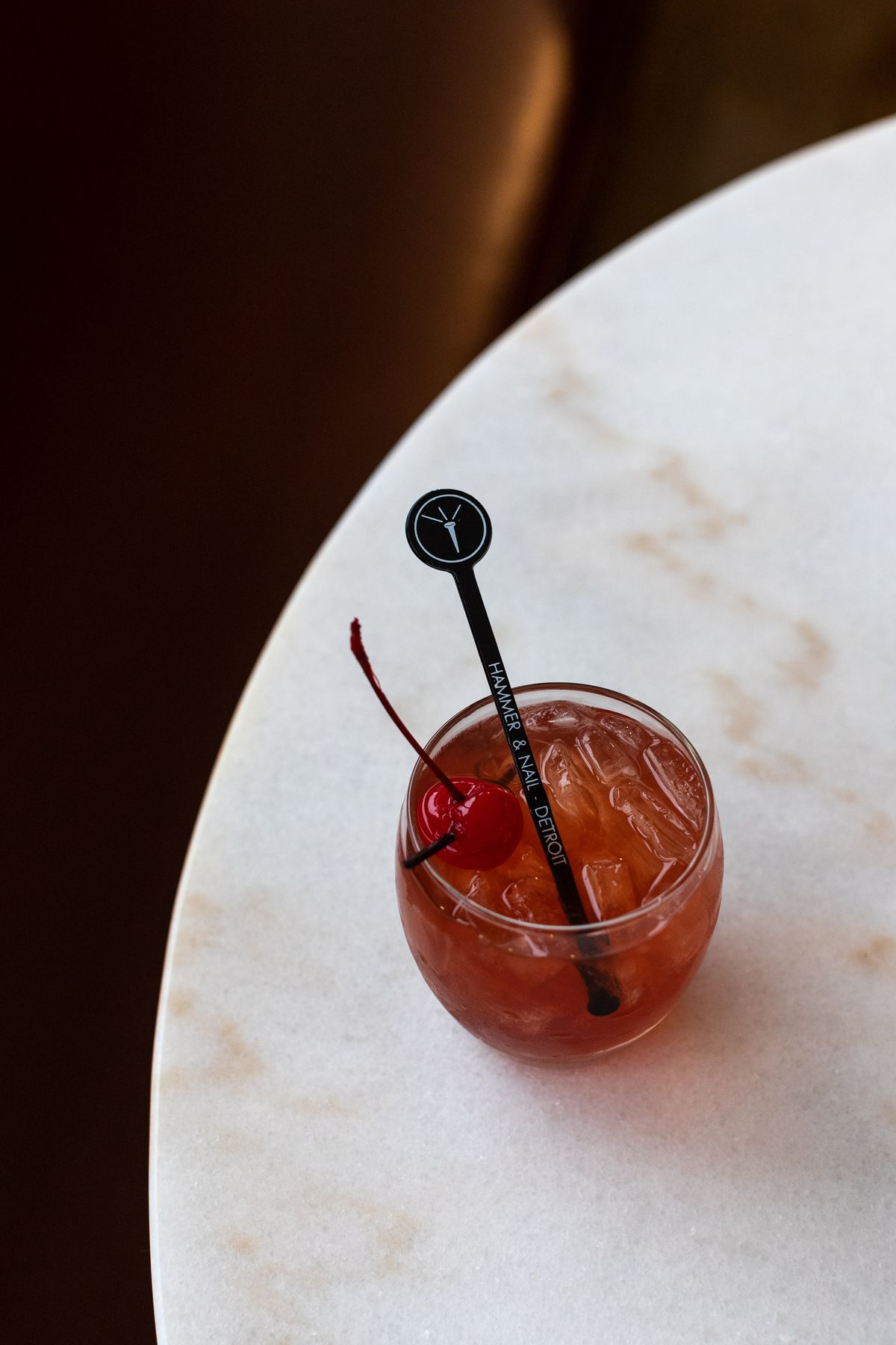A cocktail in a curved glass with ice, a cherry, and a hammer and nail swizzel stick is shown from above on a round, white marble table.