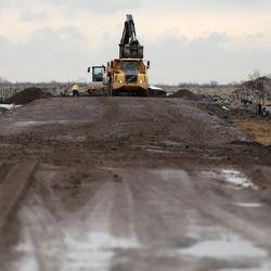 Workers repair a soft spot in the temporary haul road for the new prison in Salt Lake City on Wednesday, Feb. 22, 2017.