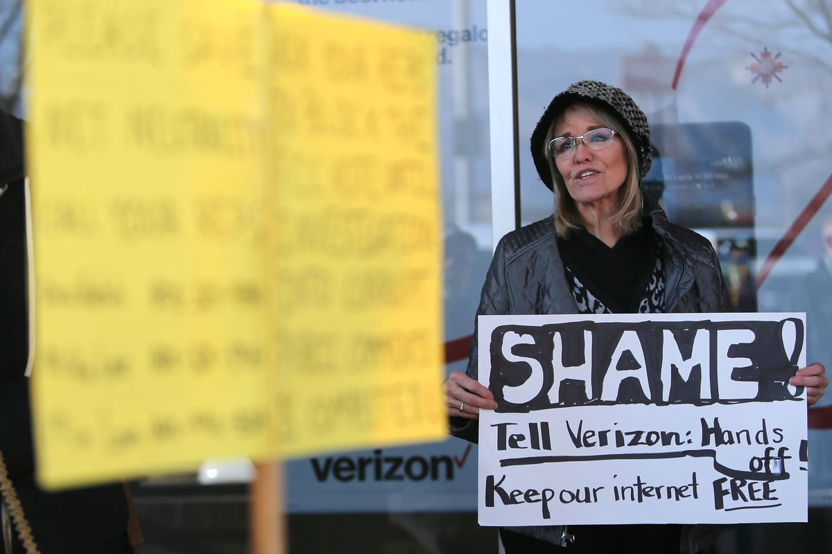 Ty Markham protests a pending FCC proposal to roll back net neutrality regulations outside a Verizon store in Salt Lake City on Thursday, Dec. 7, 2017.