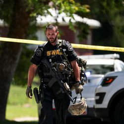 A law enforcement officer leaves the scene of an officer-involved shooting on Jackson Avenue in Ogden on Thursday, May 28, 2020.