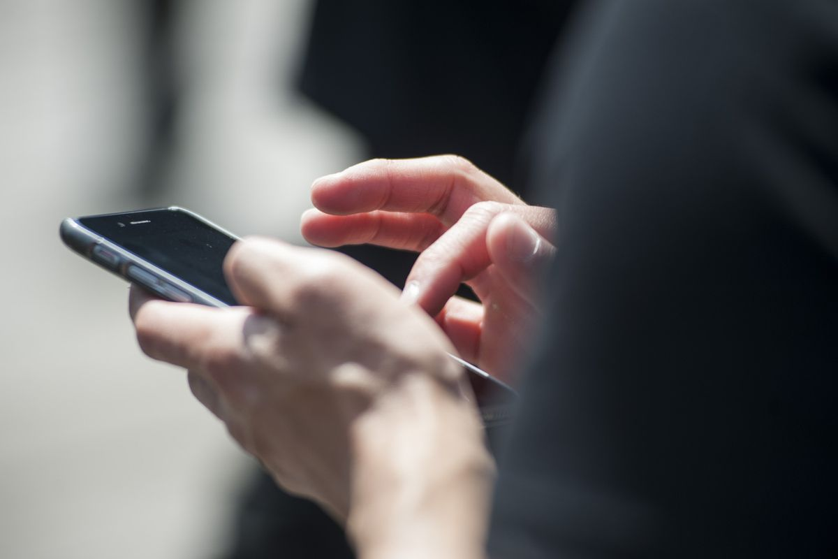Hands hold a smartphone and tap its screen