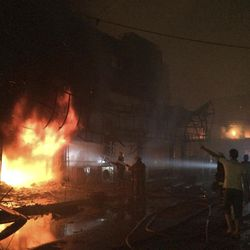 Iraqi firefighters extinguish a fire as civilians gather after a car bomb at a commercial area in Karada neighborhood, Baghdad, Iraq, early Sunday, July 3, 2016. Bombs went off early Sunday in two crowded commercial areas in Baghdad.