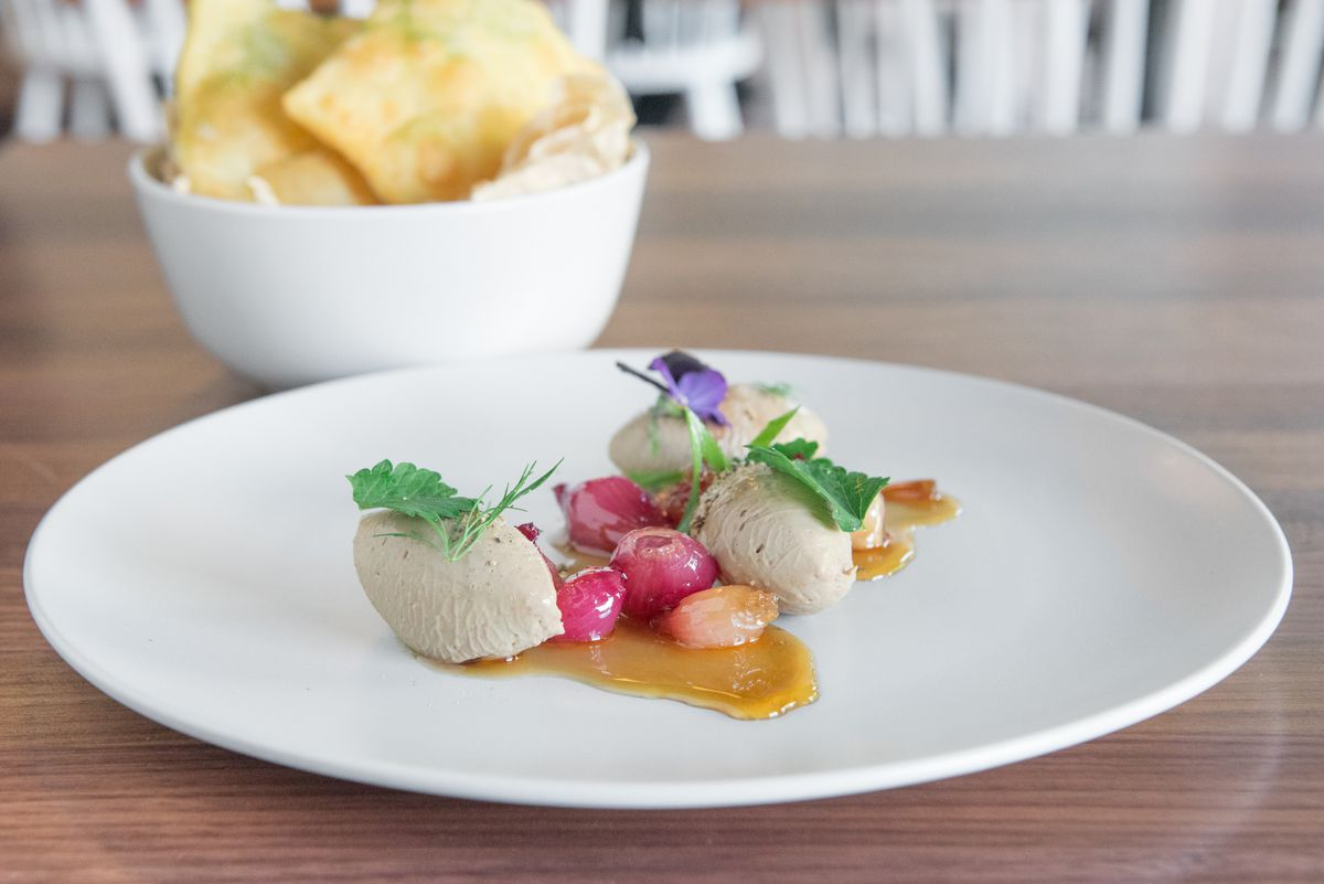 A closeup of duck liver mousse garnished with pearl onions on a white plate.