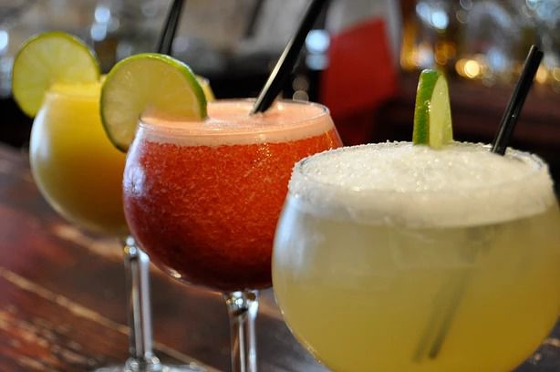 Three margarita glasses garnished with limes