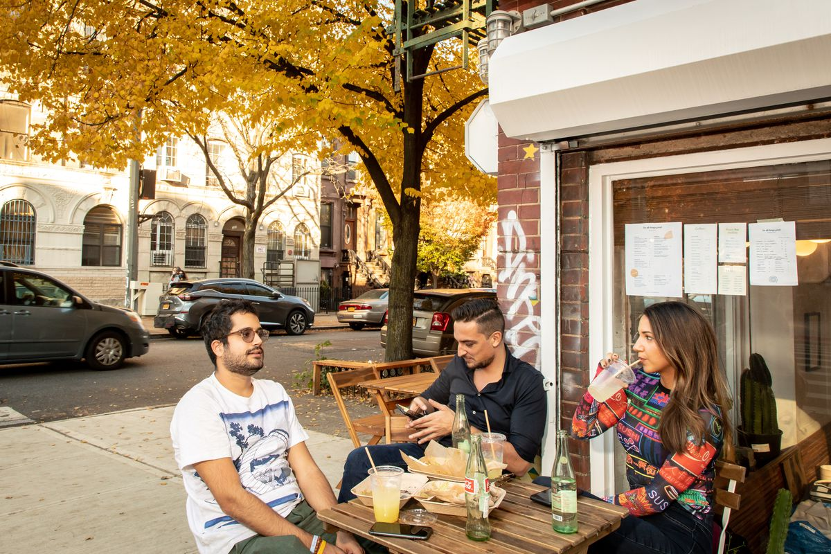 Three patrons sit at a corner outdoor table at For All Things Good; one checks his phone while another sips at aqua fresca