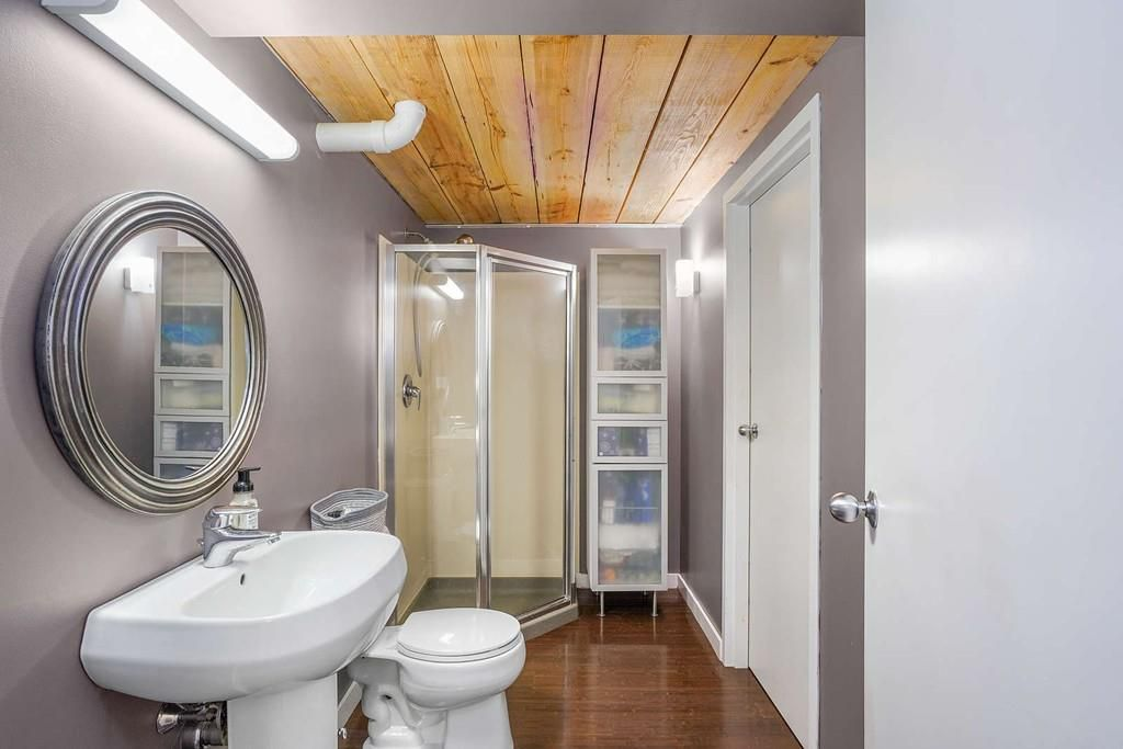 A long bathroom with a glass-doored shower at one end.