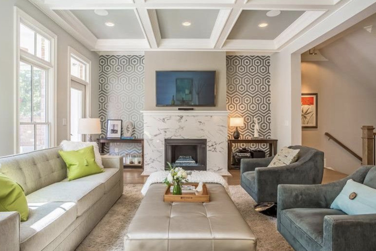 Living room with coffered ceilings, fireplace and large windows.