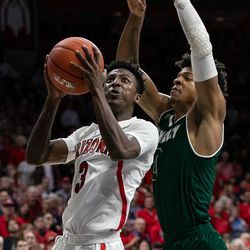 Utah Valley's Isaiah White, right, comes down on top of Arizona's Dylan Smith (3) for a block during the Arizona-Utah Valley game in McKale Center on December 6 in Tucson, Ariz.