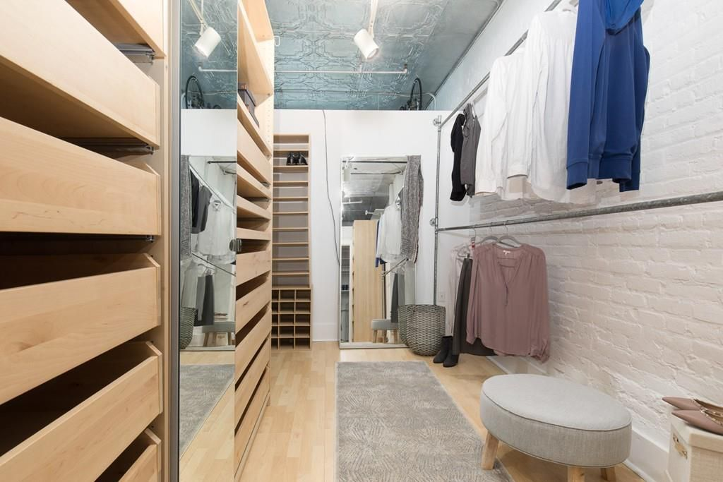 A large walk-in closet with a long pole for hanging clothes and lots of drawers for storing them.
