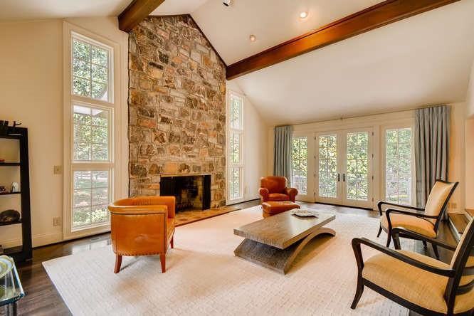 A huge white room with a stacked stone fireplace and white, orange, and leather chairs.